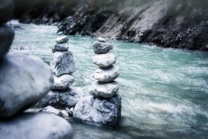 Steine sind in Balance neben einem Fluss