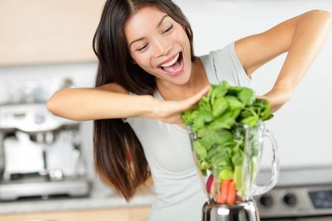Eine Frau steckt Lebensmittel, die glücklich machen, in einen Mixer