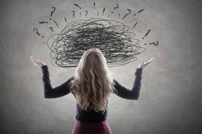 Eine Frau steht vor einem Gedankenwirrwarr, welches durch ineinander verwobene Kreise, die auf eine Wand gemalt sind, veranschaulicht wird.