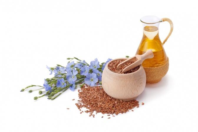 Leinsamenöl in einer Kanne neben Leinsamen und Blüten