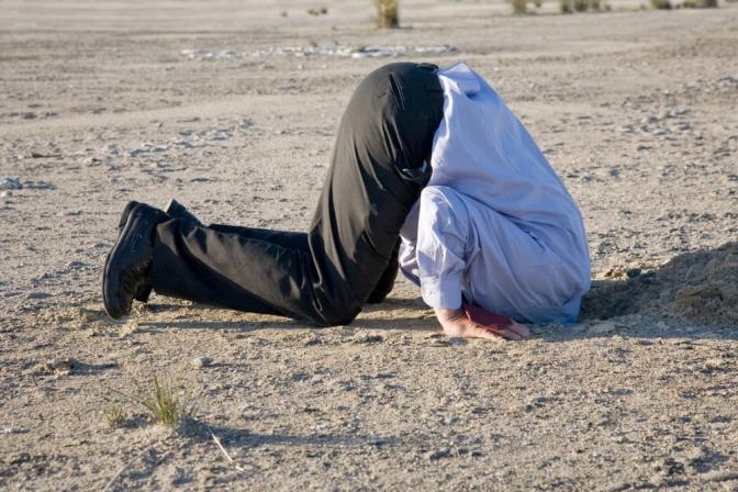 Ein Mann steckt seinen Kopf in den Boden wie ein Strauß.
