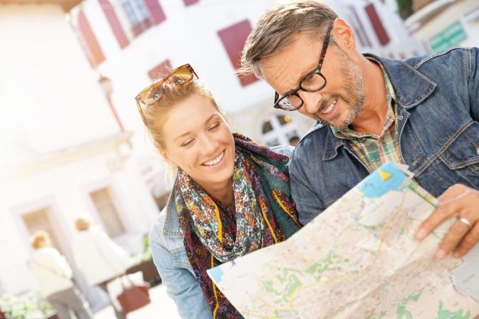 Ein Paar sieht auf eine Landkarte und kann mit Unternehmungen seine Liebe beweisen