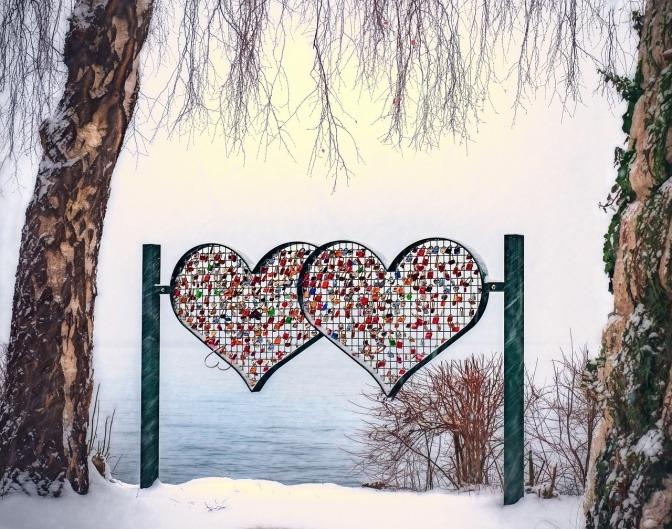 Zwei Herzen aus Metallgitter symbolisieren Grenzen
