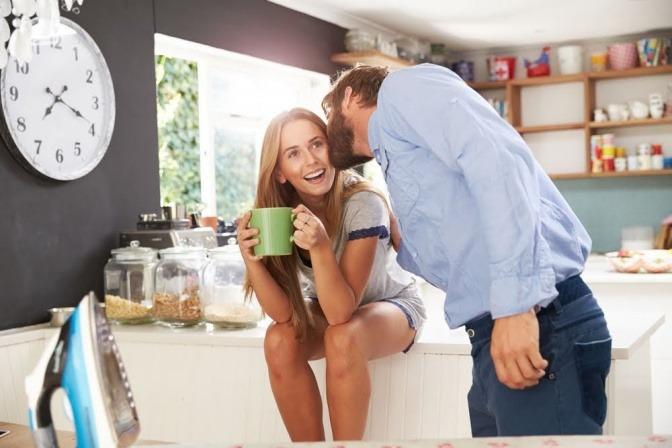 Eine Frau hockt lächelnd auf dem Küchentisch und hält eine Tasse in der Hand, während ihr Mann ihr einen Kuss auf die Wange gibt.