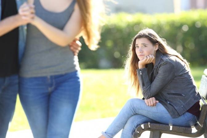 Eine Frau sitzt alleine auf einer Parkbank und blickt einem vorbeilaufenden Pärchen schmachtend hinterher.