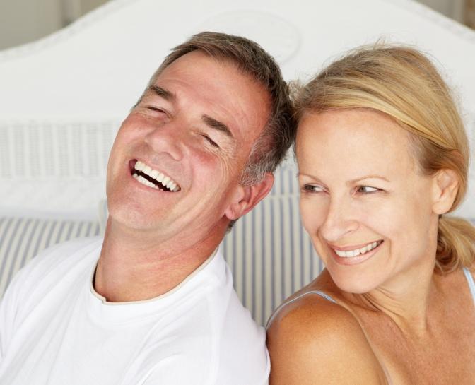 Paar um die 50 lächelt sich an