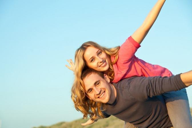 Ein Mann trägt seine Frau Huckepack und beide lächeln in die Kamera.