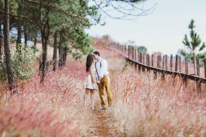 Ein liebendes Paar küsst sich stehend in der Wiese