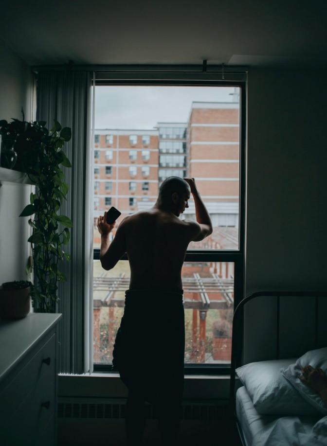Ein Mann mit nacktem Oberkörper steht am Fenste wegen Liebesentzug