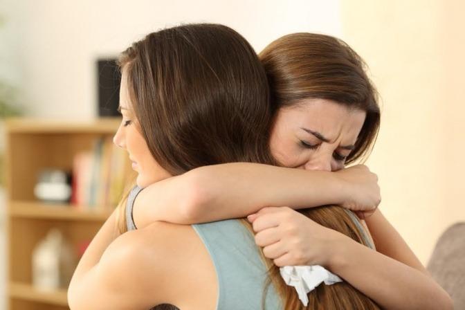 Eine Frau umarmt weinend eine andere Frau