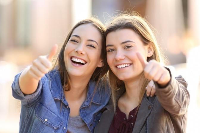 """Zwei Freundinnen zeigen die """"Daumen hoch"""" Geste."""