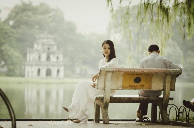 Ein Liebespaar sitzt wartend auf einer Bank