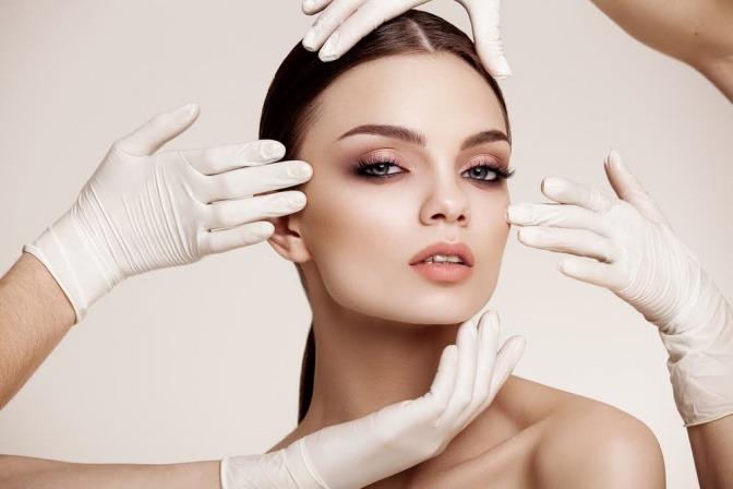 Viele Hände greifen auf das Gesicht einer Frau
