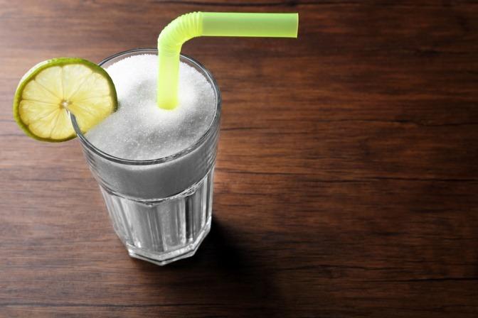 Glas voller Zucker mit Strohhalm