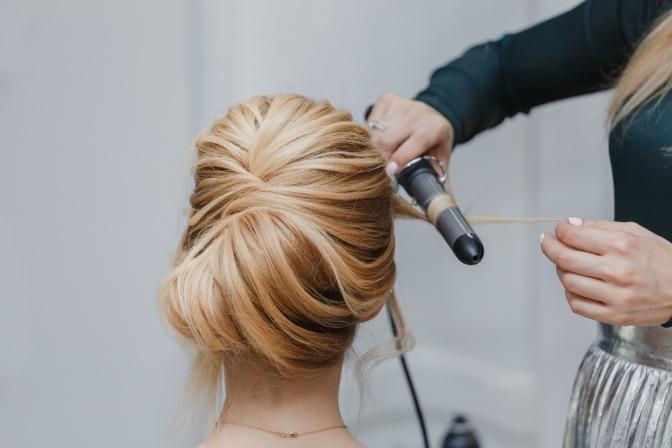 Eine Friseurin setzt den Lockenstab an einer klassischen Hochsteckfrisur an