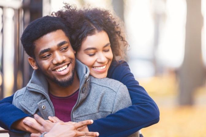Eine junge Frau umarmt von hinten lachend einen jungen Mann