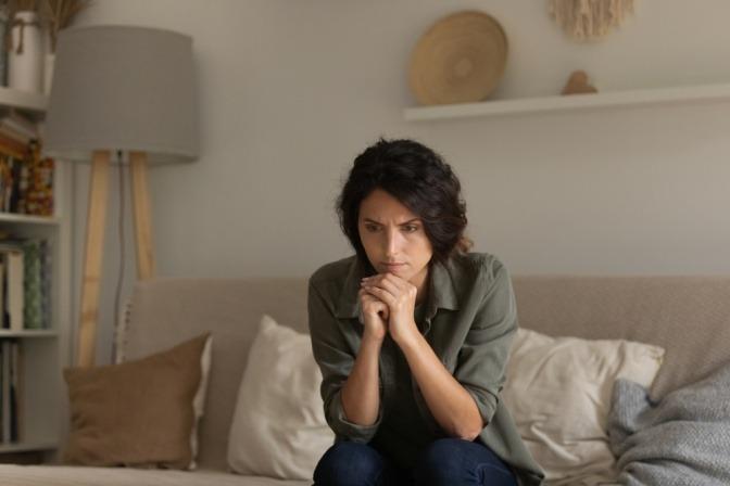 Eine nervöse Frau sitzt auf dem Sofa und versucht, ihre negativen Emotionen unter Kontrolle zu halten.