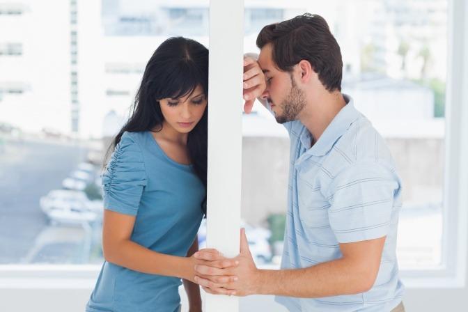 Eine Frau und ein Mann sind durch eine Wand getrennt und halten sich an den Händen