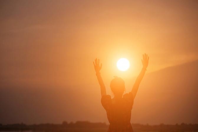 Jemand hält im Sonnenlicht die Hände hoch
