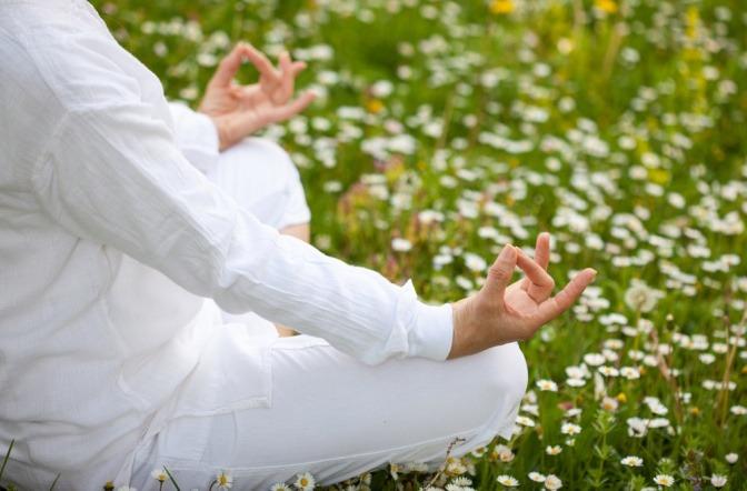 Frau in weiß in Meditationshaltung am Boden im Lotussitz