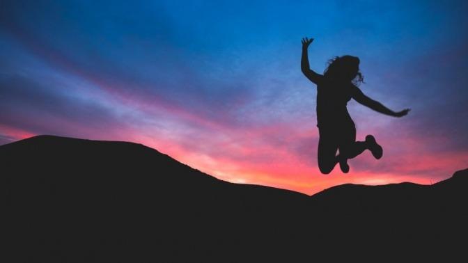 Eine Frau macht im Sonnenuntergang einen Luftsprung