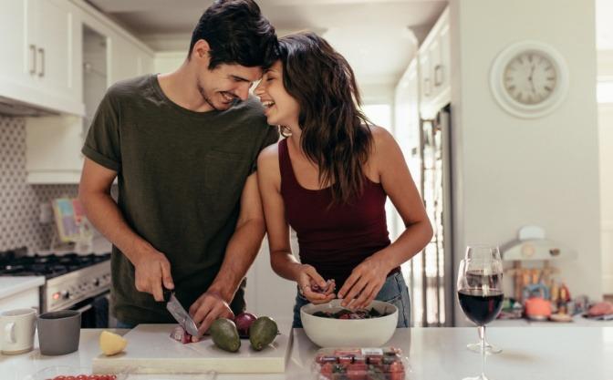 Junges glückliches Paar kocht zusammen und hat viel Spass dabei.