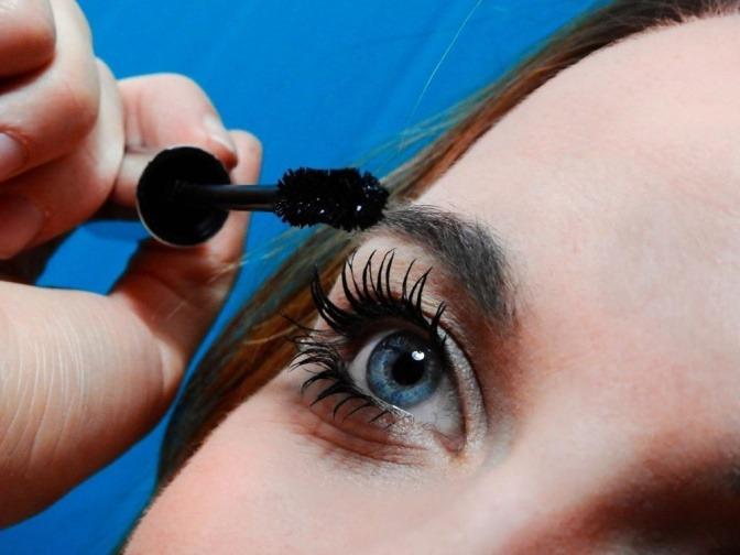 Eine Frau trägt Mascara auf ihre Augen auf