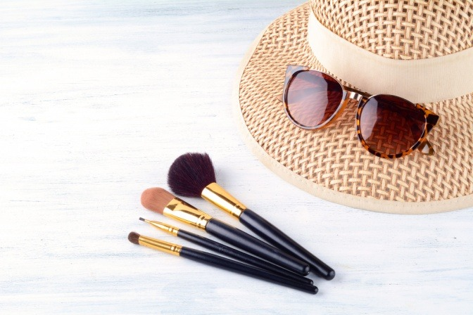 Sonnenhut, Sonnenbrille und Schminkpinsel