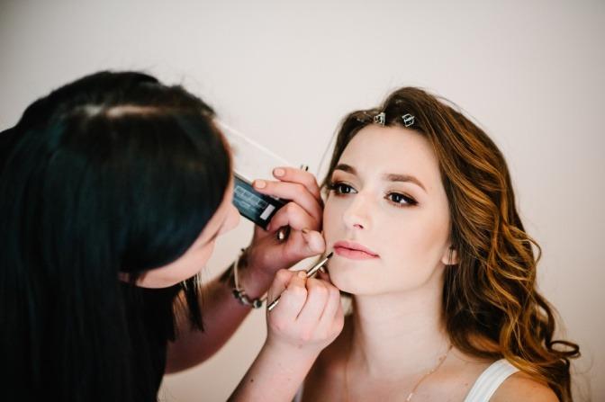 Eine Visagistin schminkt eine Frau