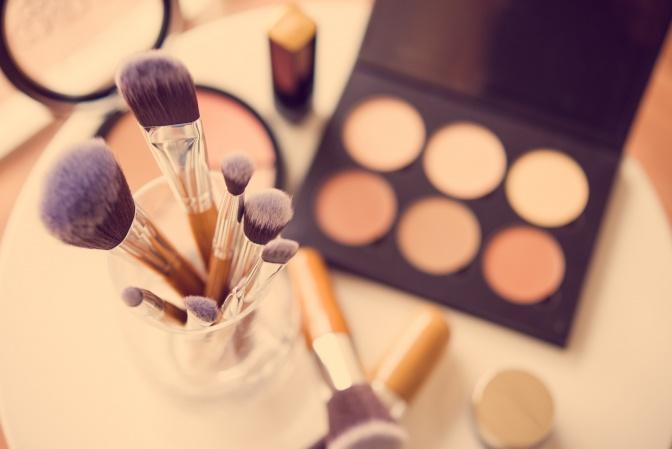 Bei einer Make-up Palette liegen Pinsel zum Schminken
