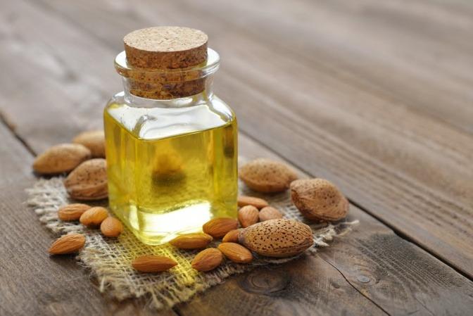 Ein Fläschchen mit Mandelöl steht neben Mandeln