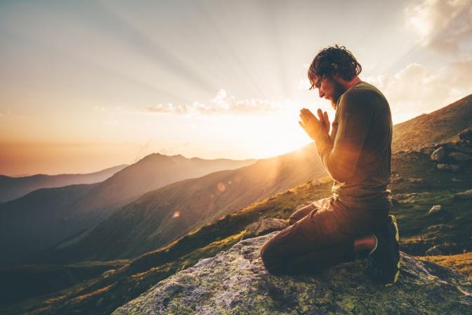 Ein Mann betet auf einem Berggipfel