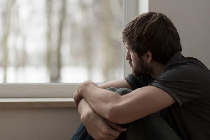 Ein Mann sieht traurig aus dem Fenster