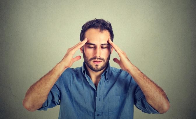 Ein Mann hält seine Finger an seine Stirn