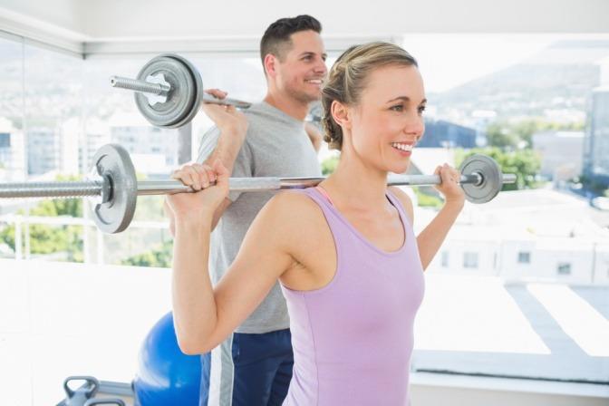 Ein Mann und eine Frau machen Sport und halten eine Hantel