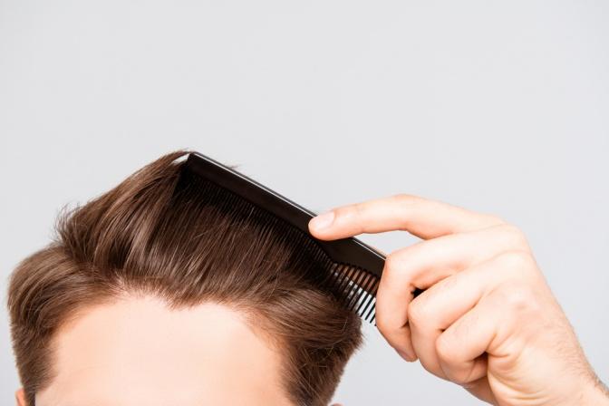 Ein Mann gibt Haarpflege in seine Haare