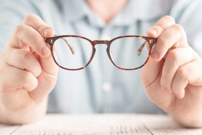 Ein Mann hält eine braune Brille in der Hand