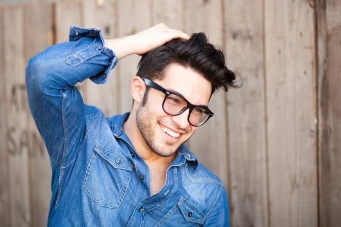 Junger Mann mit schönen Haaren und Brille.