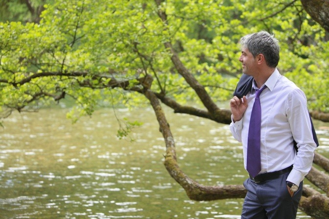 Ein Mann im Anzug befindet sich am Ufer eines Flusses