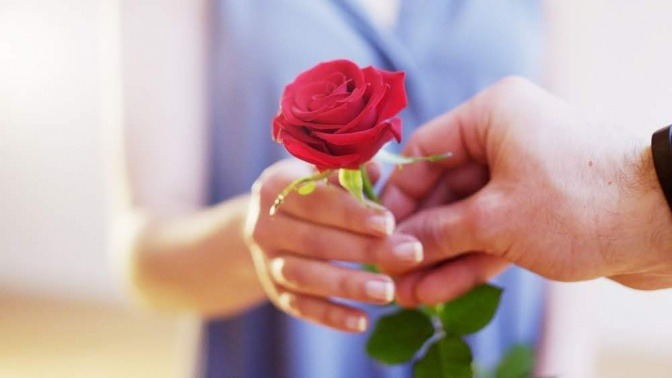 Ein Mann gibt einer Frau eine rote Rose