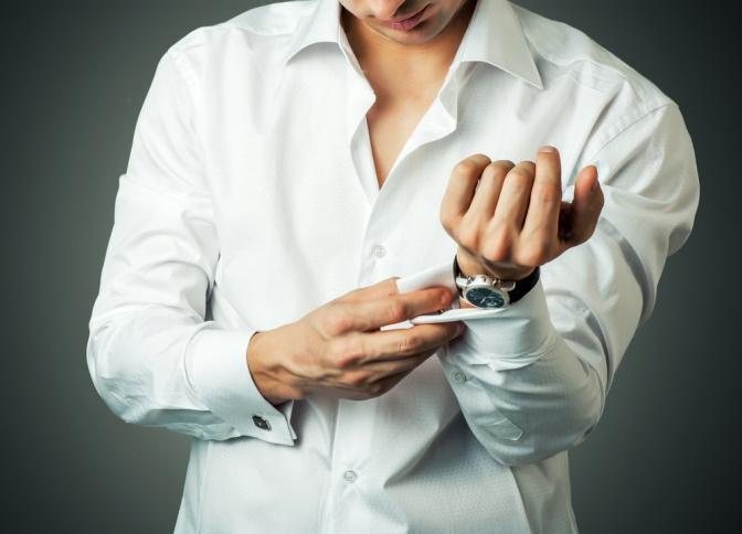 Ein Mann trägt einen Manschettenknopf auf seinem Hemd