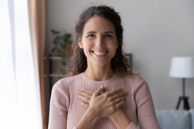 Porträit einer lächelnden Frau, die ihre Hände verschränkt auf ihre Brust legt