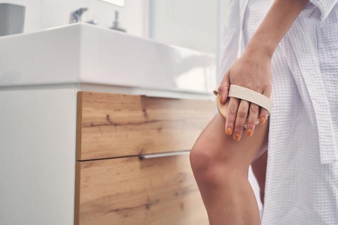 Frau massiert ihr Bein mit einer Massagebürste gegen Cellulite