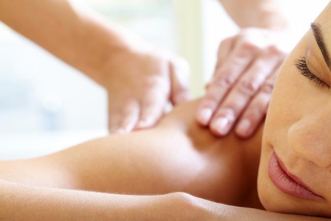 Eine Frau erhält eine Massage bei Rückenschmerzen