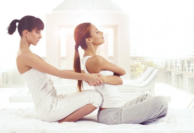 Zwei Frauen führen die Massagetechnik Thai Massage durch
