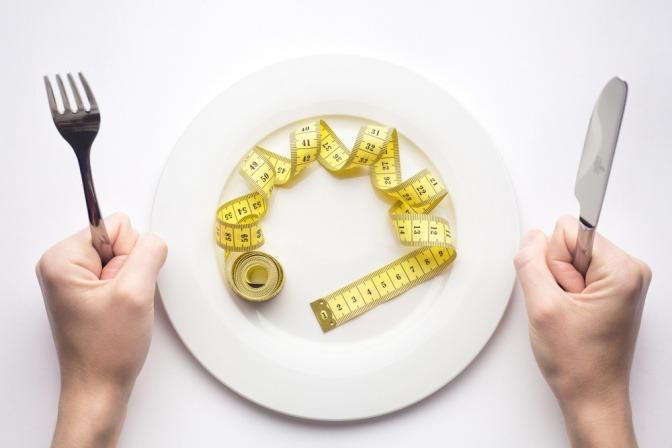 Gabel mit Maßband auf einem leeren Teller