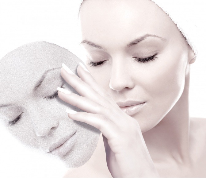 Eine Frau hält eine Maske mit der Form ihres Gesichts vor ihr
