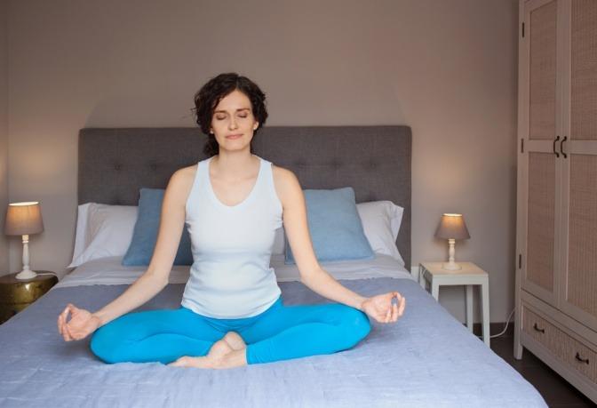 Eine Frau meditiert entspannt im Bett