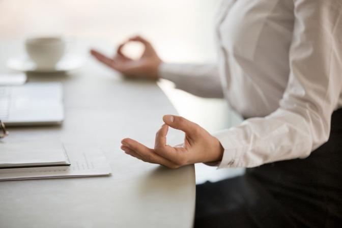 Frau meditiert am Arbeitsplatz