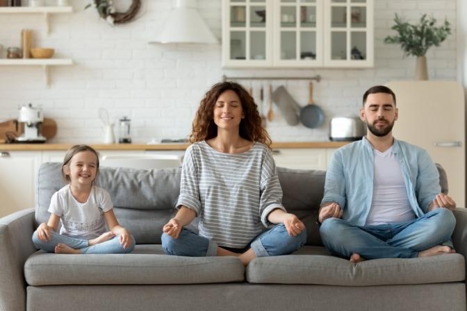 Eine kleine Familie meditiert auf der Couch als Morgenritual